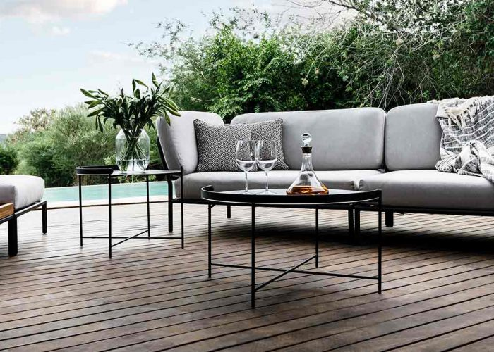 Houe 3seter sofa i tre og sort metallramme med grå puter og et rundt sort metallbord